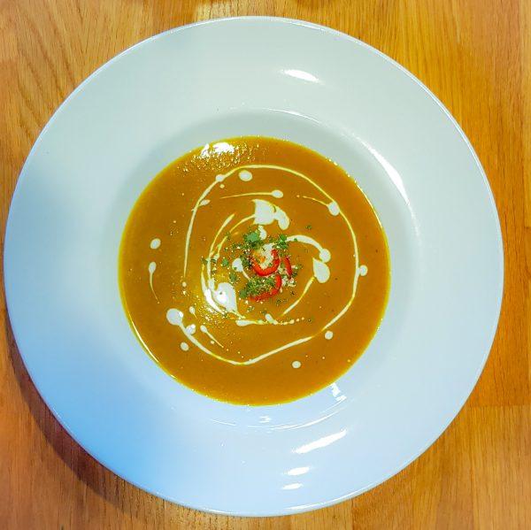 Zet het vuur uit en pureer de soep totdat deze helemaal glad is. Roer er nu de helft van de kokosroom door. Serveer de warme soep en garneer met de overgebleven kokosroom, rode peper en verse koriander. Smakelijk!