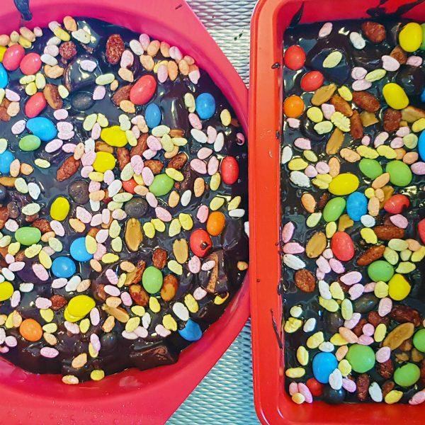 Snijd alle lekkere ingrediënten die je hebt gekozen in stukjes. Roer dit door het chocolademengsel heen en roer goed door. Schenk het mengsel in één of meerdere bakvormen, afhankelijk van de grootte. Strooi hier ook nog wat gekleurde ingrediënten overheen. Laat het afgedekt ten minste 2 uur afkoelen in de koelkast. Snijd de rocky road in kleine stukjes. Smakelijk!