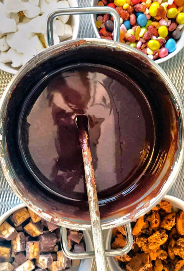 Breek de chocolade in stukjes. Snijd de boter in kleine blokjes. Smelt de chocolade, boter en stroop in een grote pan of au bain marie boven kokend water. Blijf hoe dan ook goed roeren zodat de chocolade niet aanbrandt. Blijf roeren totdat alles is gesmolten.