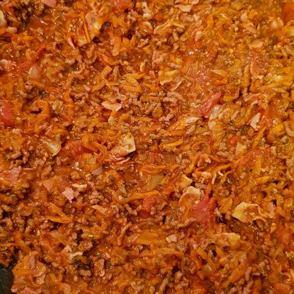 Schil de winterpeen en rasp deze. Voeg ook de geraspte wortel toe aan de pan. Bak dit kort mee, het moet namelijk nog knapperig blijven. Voeg de tomatenpuree toe en bak dit een paar minuten mee. Voeg vervolgens de tomaten uit blik toe. Voeg niet al het tomatensap toe anders wordt de saus te vochtig en de wortel te slap. Voeg nu een flinke scheut rode wijn en het runderbouillonblokje toe. Kruid met de gedroogde Italiaanse kruiden en laat het voor ongeveer 30 minuten pruttelen.