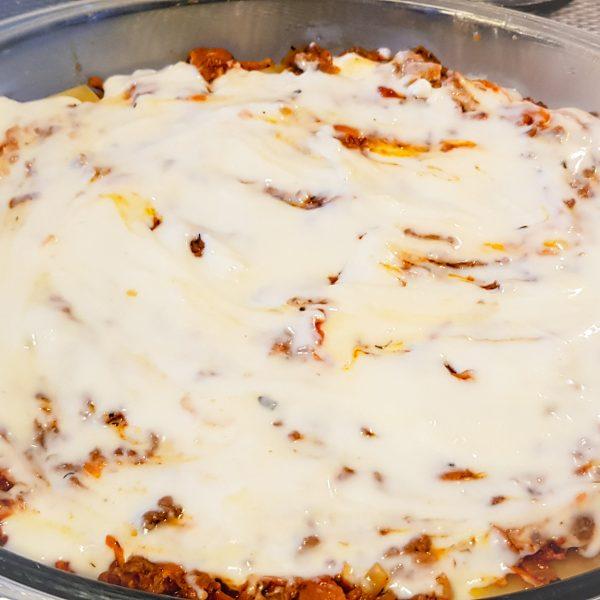 Vet een grote ovenschaal in. Begin met een dun laagje bolognesesaus, giet hier een dun laagje bechamelsaus overheen en leg hier een enkele laag gedroogde lasagnevellen op. Doe dit tot beide sauzen op zijn, je eindigt met een laag bechamelsaus. Rasp hier een goede laag parmezaanse kaas overheen.
