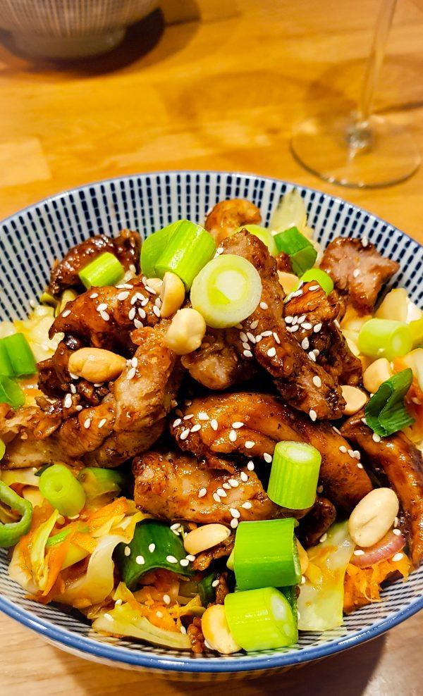 Frituur de kipreepjes in porties in de hete olie en laat dit uitlekken in een vergiet (bekleed met wat keukenpapier). Als je alle kip gebakken hebt, meng dit dat met de saus die je net in het pannetje hebt ingekookt. Verdeel de kip over de kimchi salade in de kommen en garneer met sesamzaadjes en pinda's. Smakelijk!