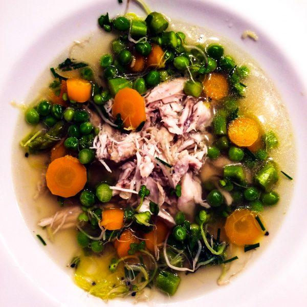 Giet de bouillon in een nieuw soeppan en kook hier de asperges, doperwten en wortel voor een paar minuutjes in totdat het beetgaar is. Verdeel de kip over 4 soepkommen of diepe borden en giet hier de kippenbouillon met groenten overheen.