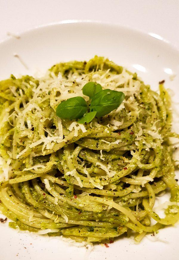 Meng de pesto door de spaghetti. Rasp hier wat zest van de citroenschil overheen en voeg evt. wat extra olijfolie toe als de pesto te droog is. Garneer met versgemalen peper, geraspte Parmezaanse kaas en basilicum.