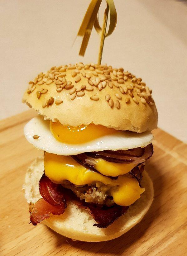 Tijd om de hamburgers samen te stellen! Snijd een hamburgerbroodje doormidden. Leg hier een plakje gebakken ham op, wat uienringen, de burger gevolgd door het kwarteleitje. Ik vind zelf dat hier geen saus meer bij nodig is, maar als je het lekker vindt kun je er not tomatenketchup en mayonaise overheen doen. Ook kun je een cherrytomaatje in plakjes snijden en deze ook toevoegen aan je hamburger.  Je burger is klaar, smakelijk!