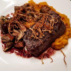 Hertenbiefstuk met zoete aardappelpuree, gemengde paddenstoelen en rode portsaus met gefrituurde enoki