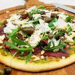 Carpaccio pizza met groene pesto, truffelmayonaise, rucola, kappertjes en pijnboompitten