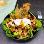 Caesar salade met een gepocheerd eitje en crispy kippenvel