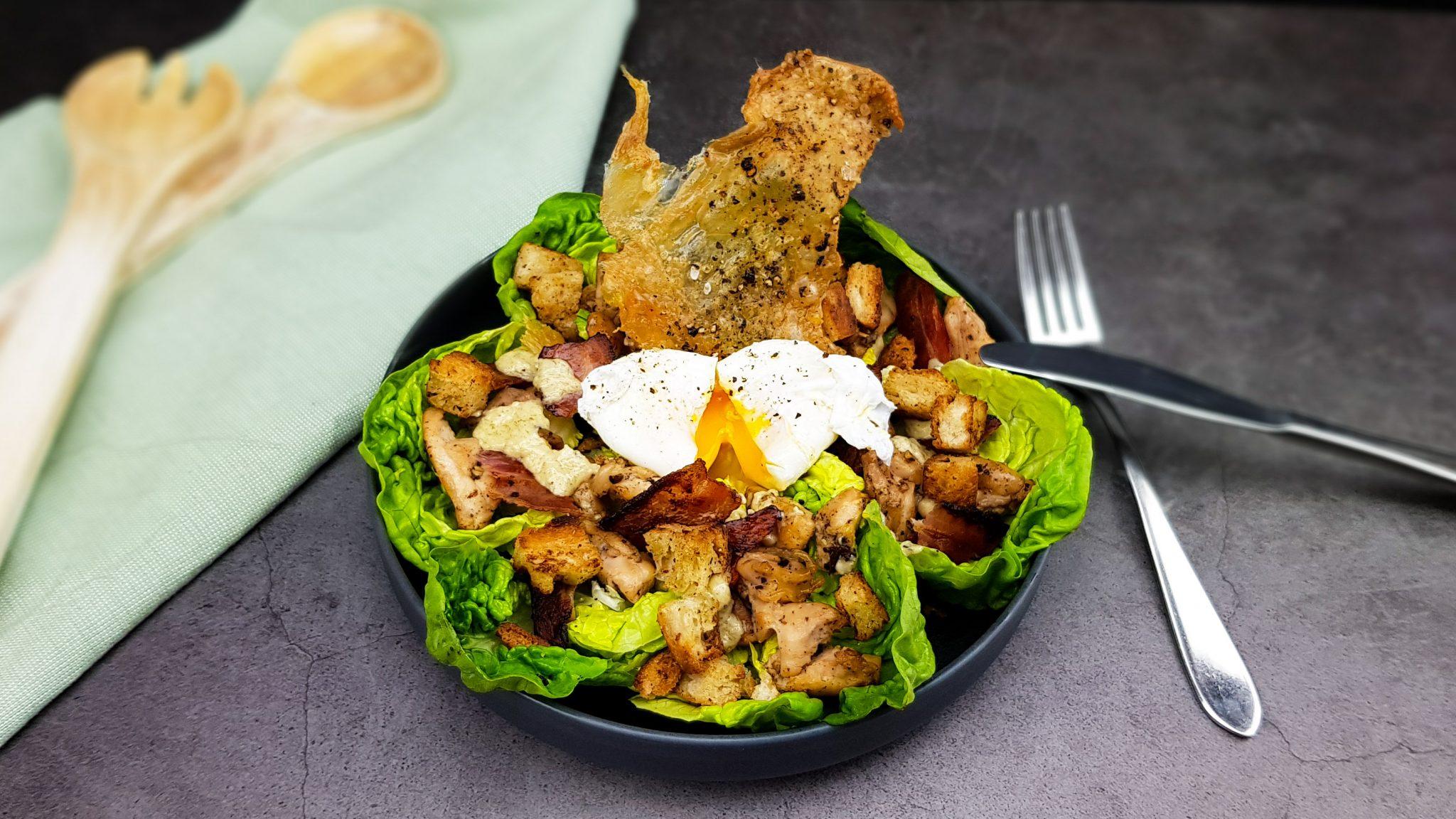 Caesar salad met een gepocheerd eitje en crispy kippenvel