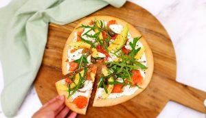 Bloemkoolpizza met gerookte zalm, roomkaas, mozzarella en avocado