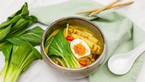 Gele currysoep met noedels, bok choy en een gekookt eitje